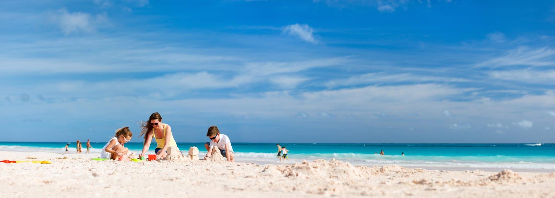 Mutter und Kinder, die Sandburg am tropischen Strand machen
