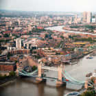 A photo of London takes from a helicopter showing the Thames river, London Bridge and several sky scrapers.