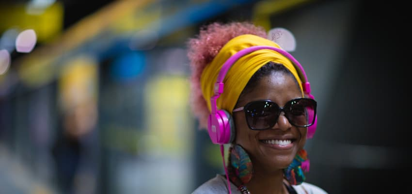 Woman with headphones in a train station.