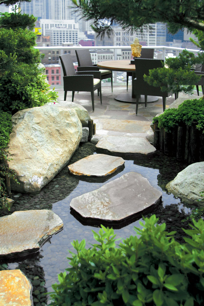 pond with rock path and view of seating area in rooftop garden