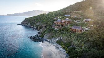treelined coastal landscape with houses, ocean, beach, hills
