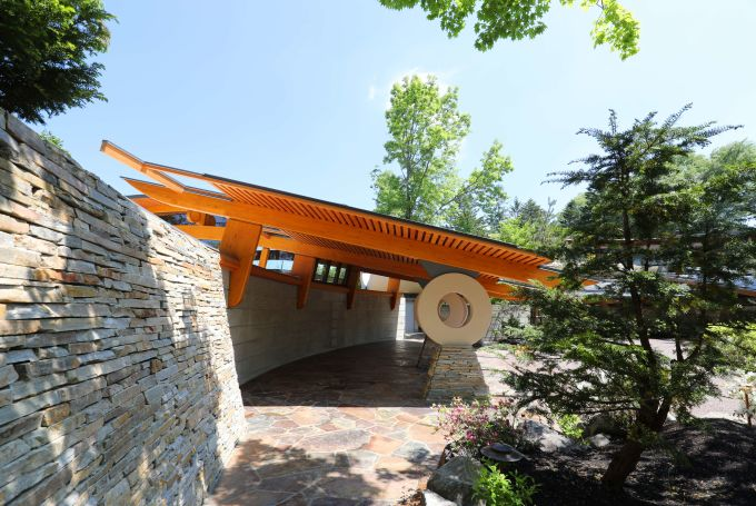 pavilion with orange roof and rock wall