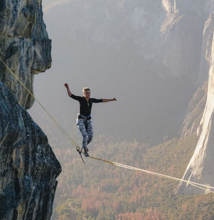 photo of a woman walking a tightrope over a cliff as a metaphor for the precarious nature of startups