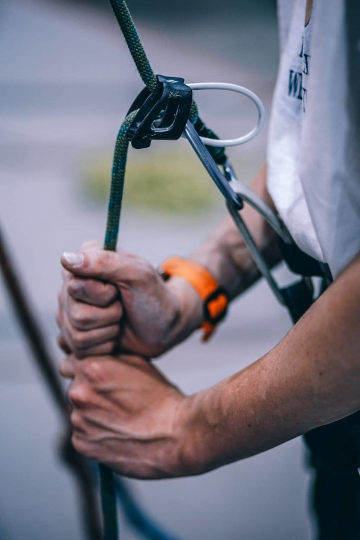 picture of someone adjusting a rock climbing safety harness