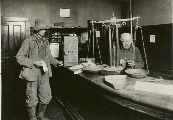 photo from new york public library digital collection showing a gold miner getting his latest haul weighed