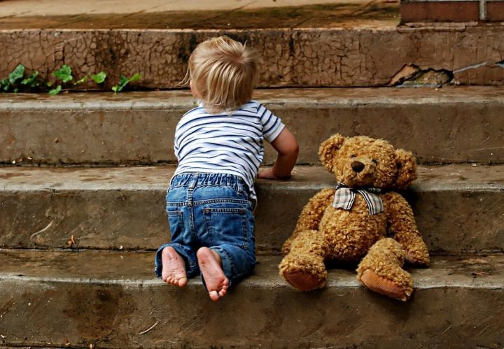 photo of a toddler crawling up steps with his teddy bear