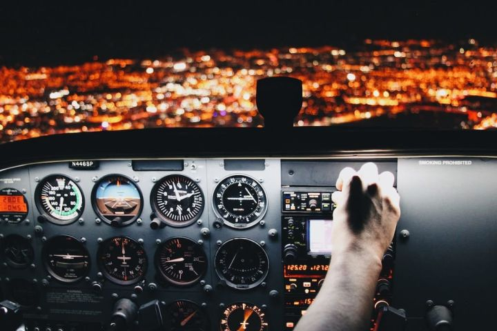 Photo of a pilot at the controls of an airplane flying at night