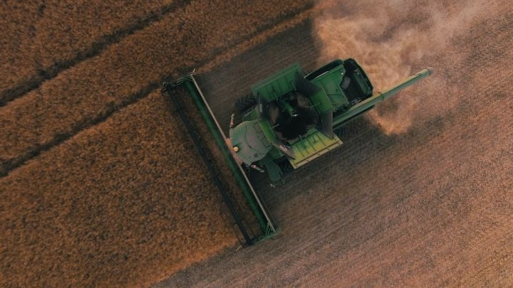 Aerial photo of a tractor plowing a field. Photo by Scott Goodwill on Unsplash
