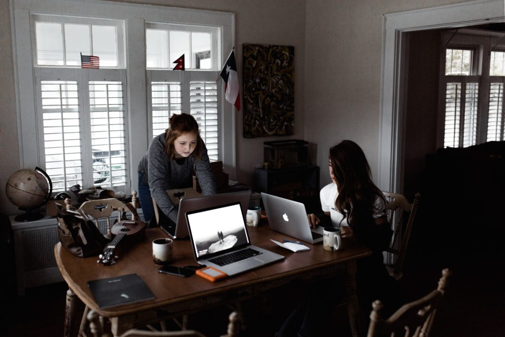 photo of two women working on laptops around a dining room table