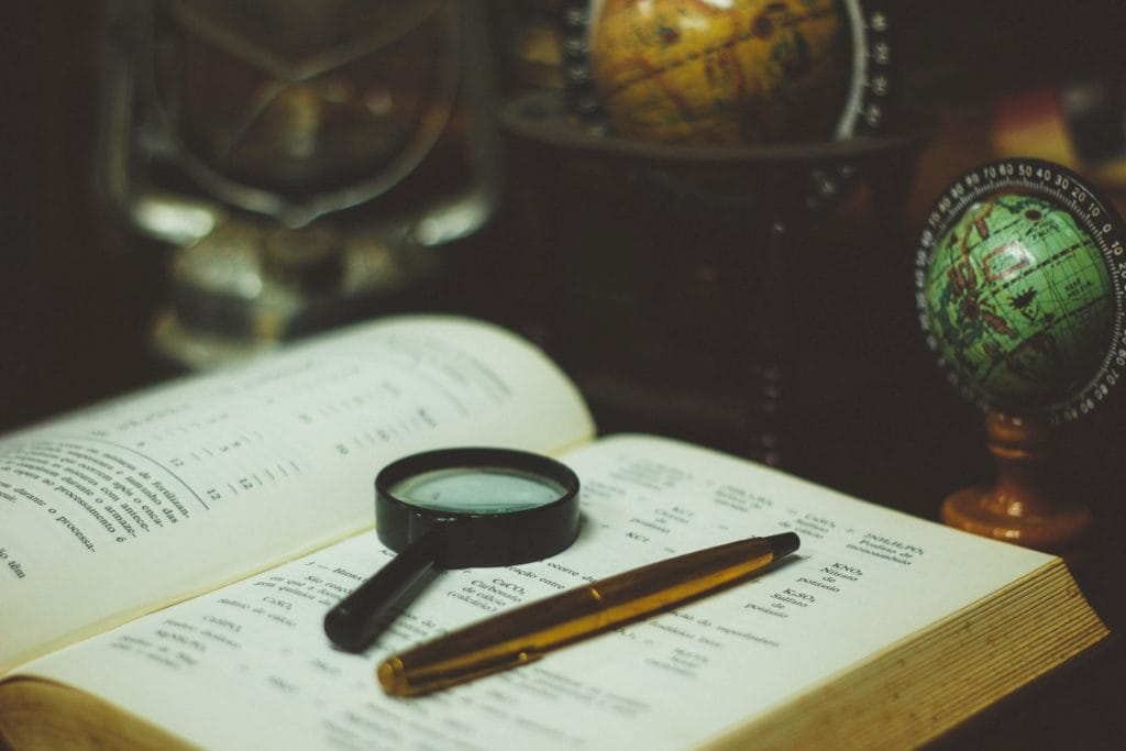 magnifying glass and pen on the top of an open book