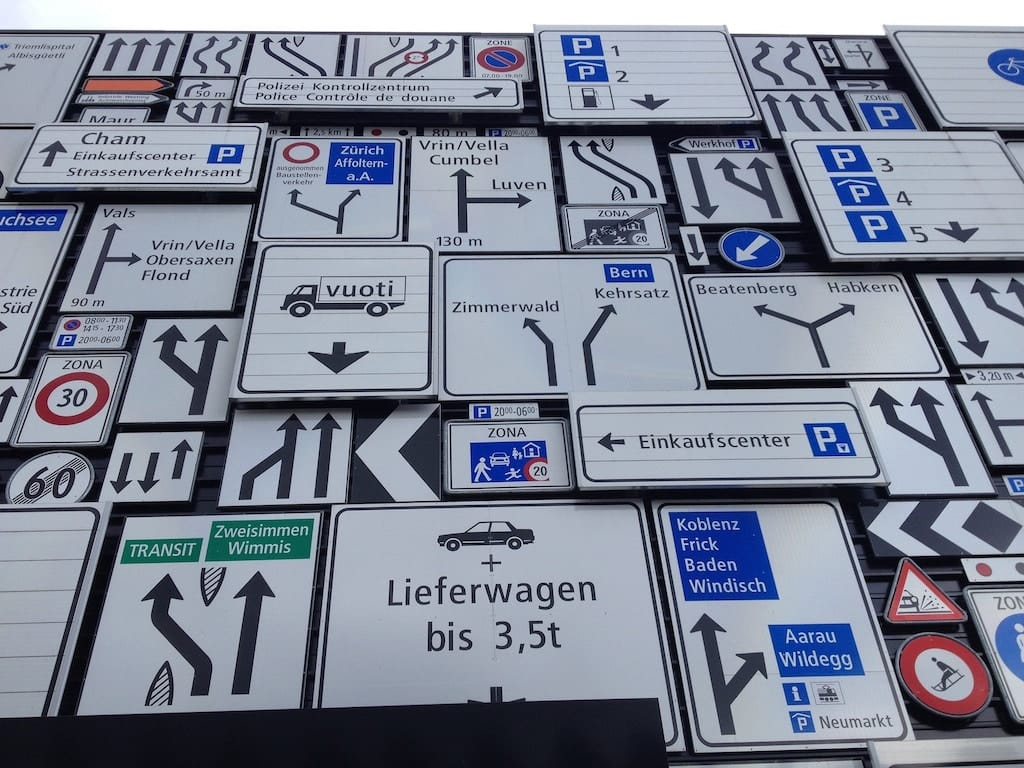 photo of an array of many confusing road signs