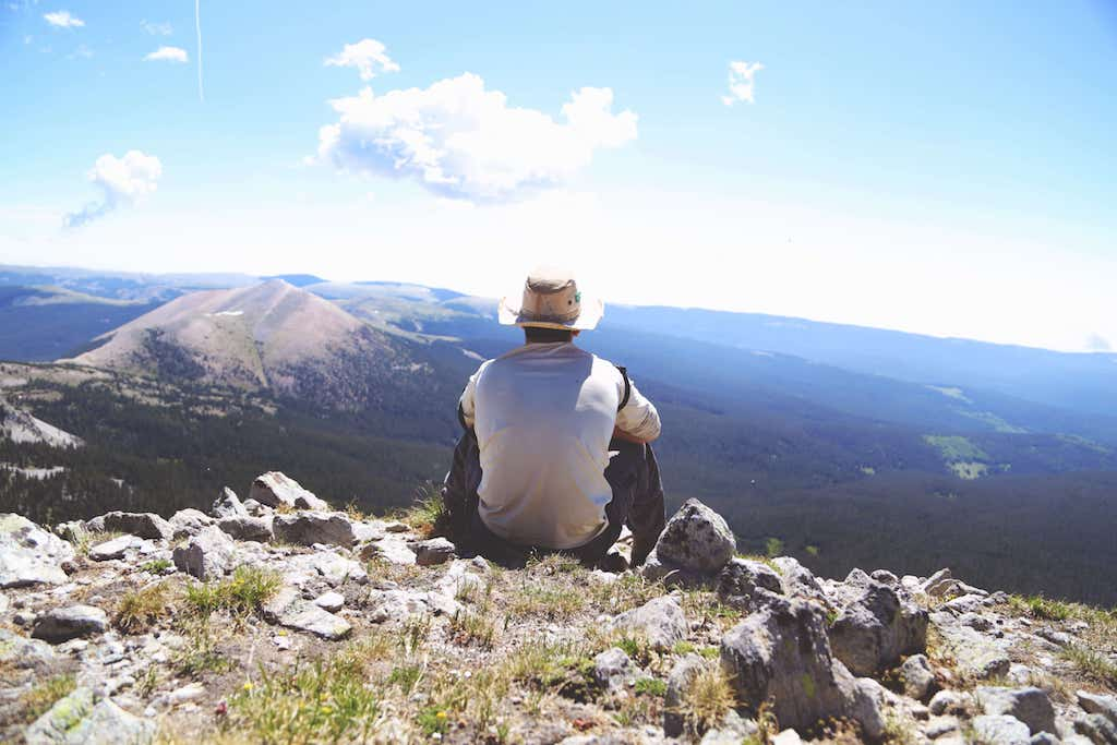 dude sitting on top of a mountain overlooking a valley, looks like someone who probably does some freelancing