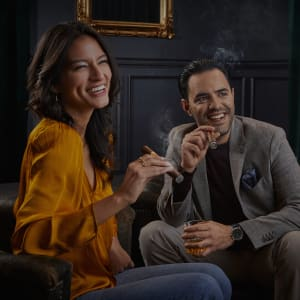 Man and woman smiling and holding lit cigars