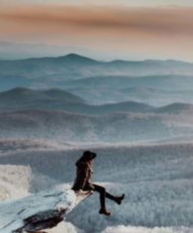 Snowy valley overlook sitting on the edge