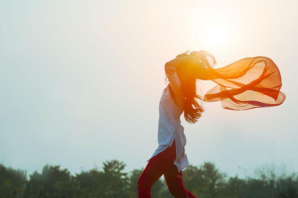 femme libre dans son corps jouant avec un drap orange