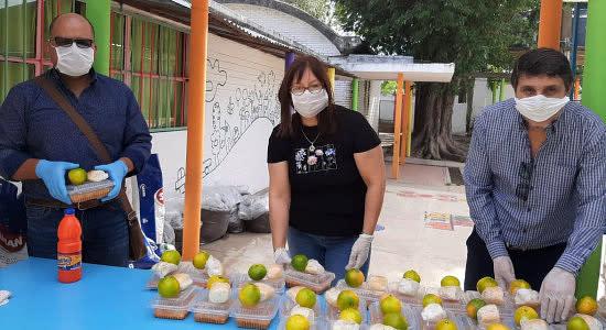Lärare med munskydd delar ut mat