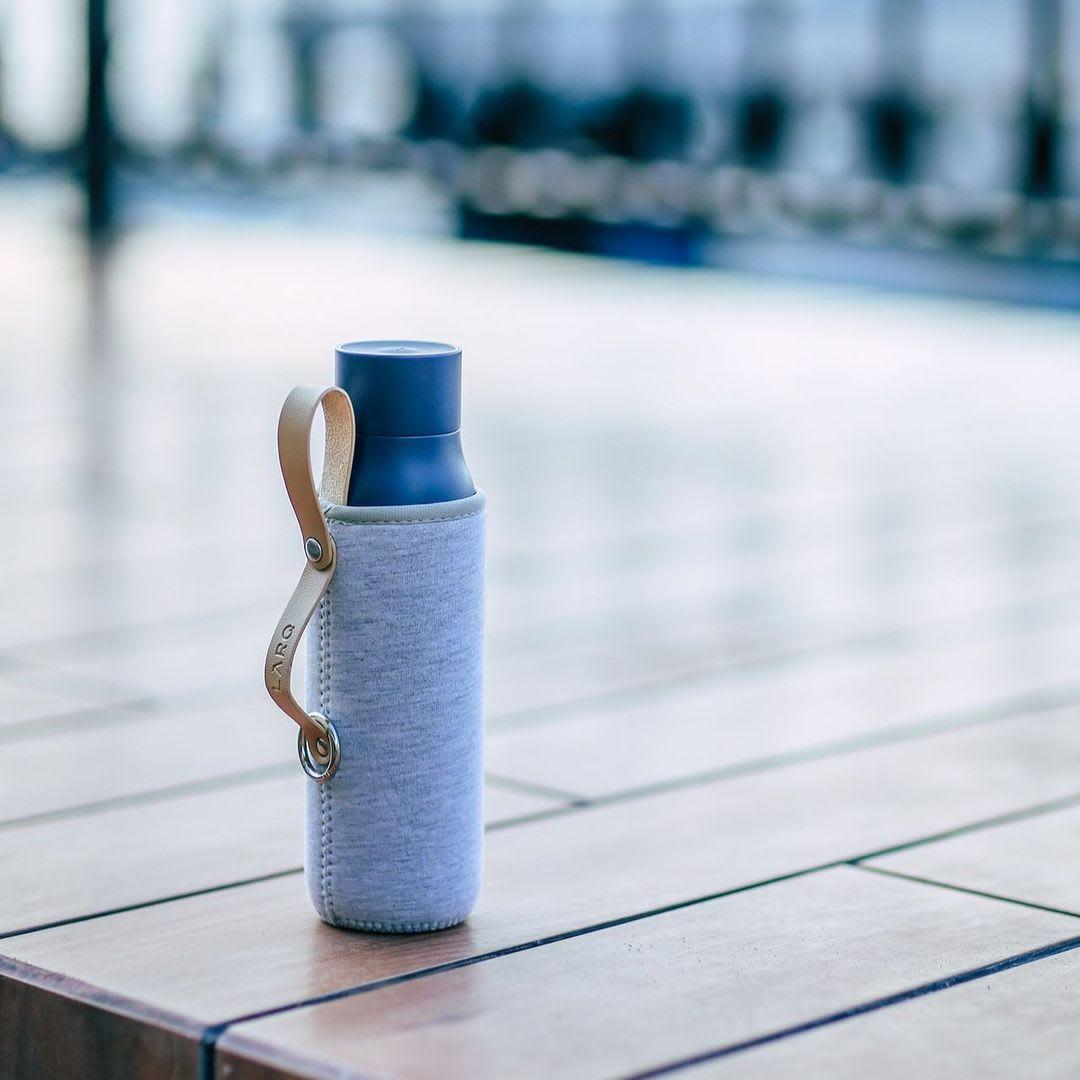 Photo of LARQ Bottle PureVis - Monaco Blue in Travel Sleeve on wooden floor