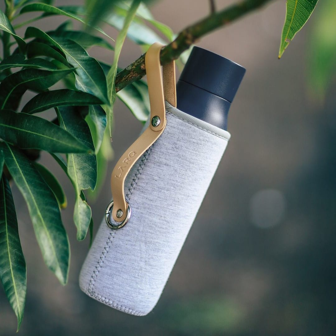 Photo of LARQ Bottle PureVis - Monaco Blue in Limited Edition Sleeve hanging on a tree
