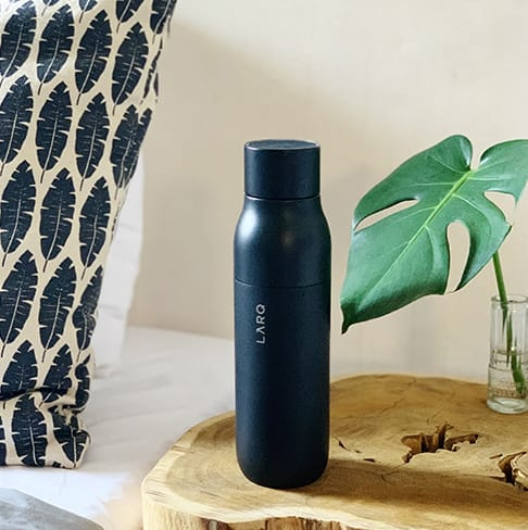 LARQ Bottle PureVis in 17oz/500ml in the color Obsidian Black sitting on a side table