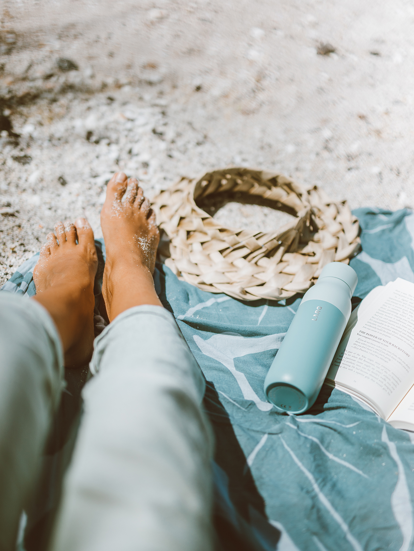 Elana Jadallah sits on blue beach towel with her seaside mint LARQ Bottle