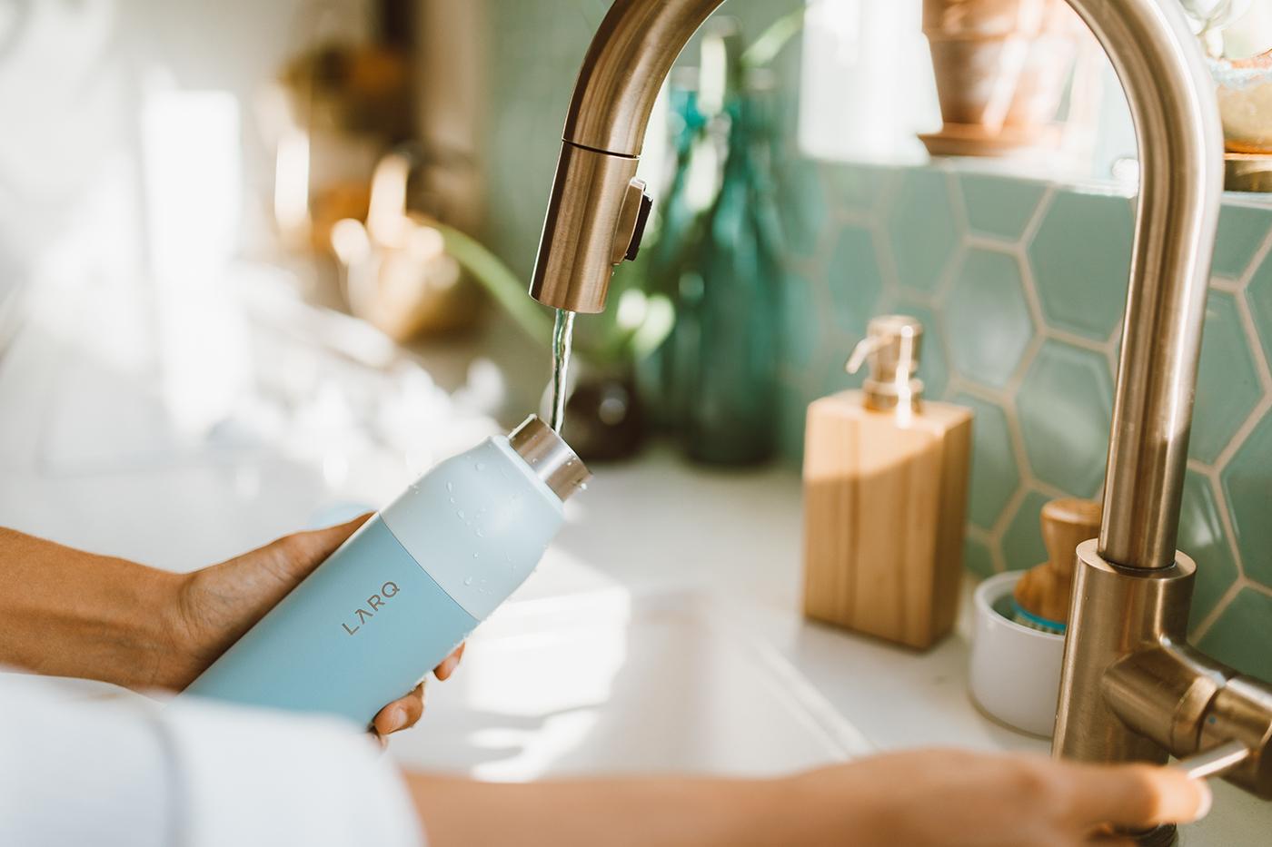 woman filling up LARQ Bottle in kitchen sink