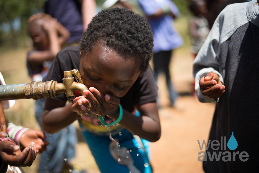African boy drinking clean drinking water from fountain