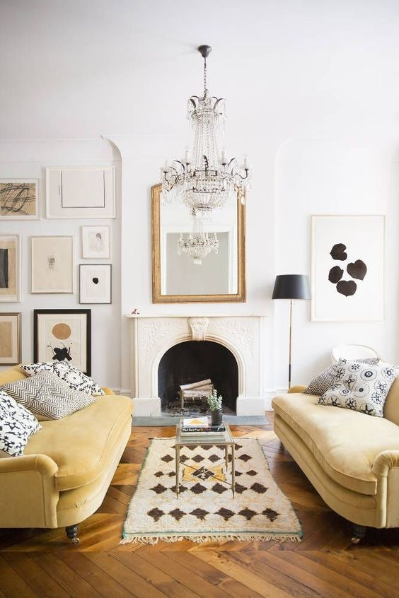 bright modern glam parisian interior design with yellow velvet couches and gilded mirror