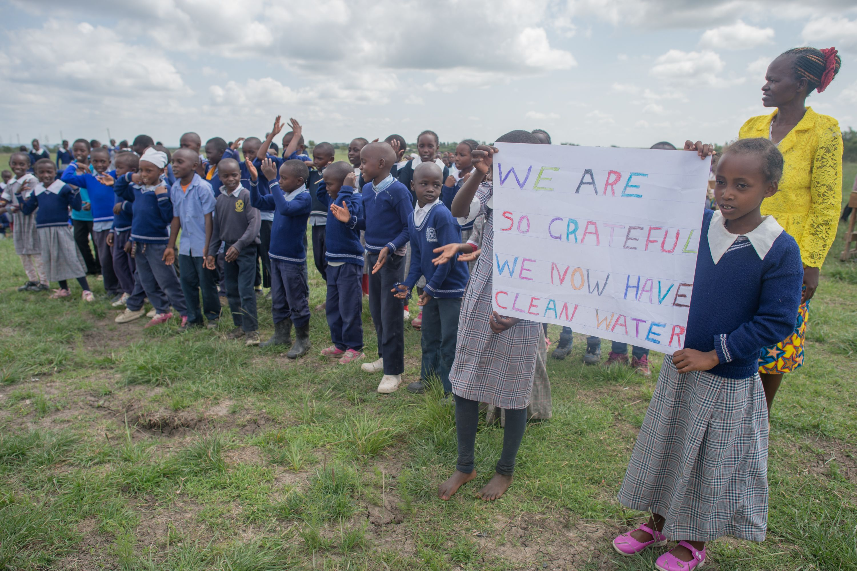 """Young students of Njoguini holding sign that says """"We are so grateful we now have clean water"""""""