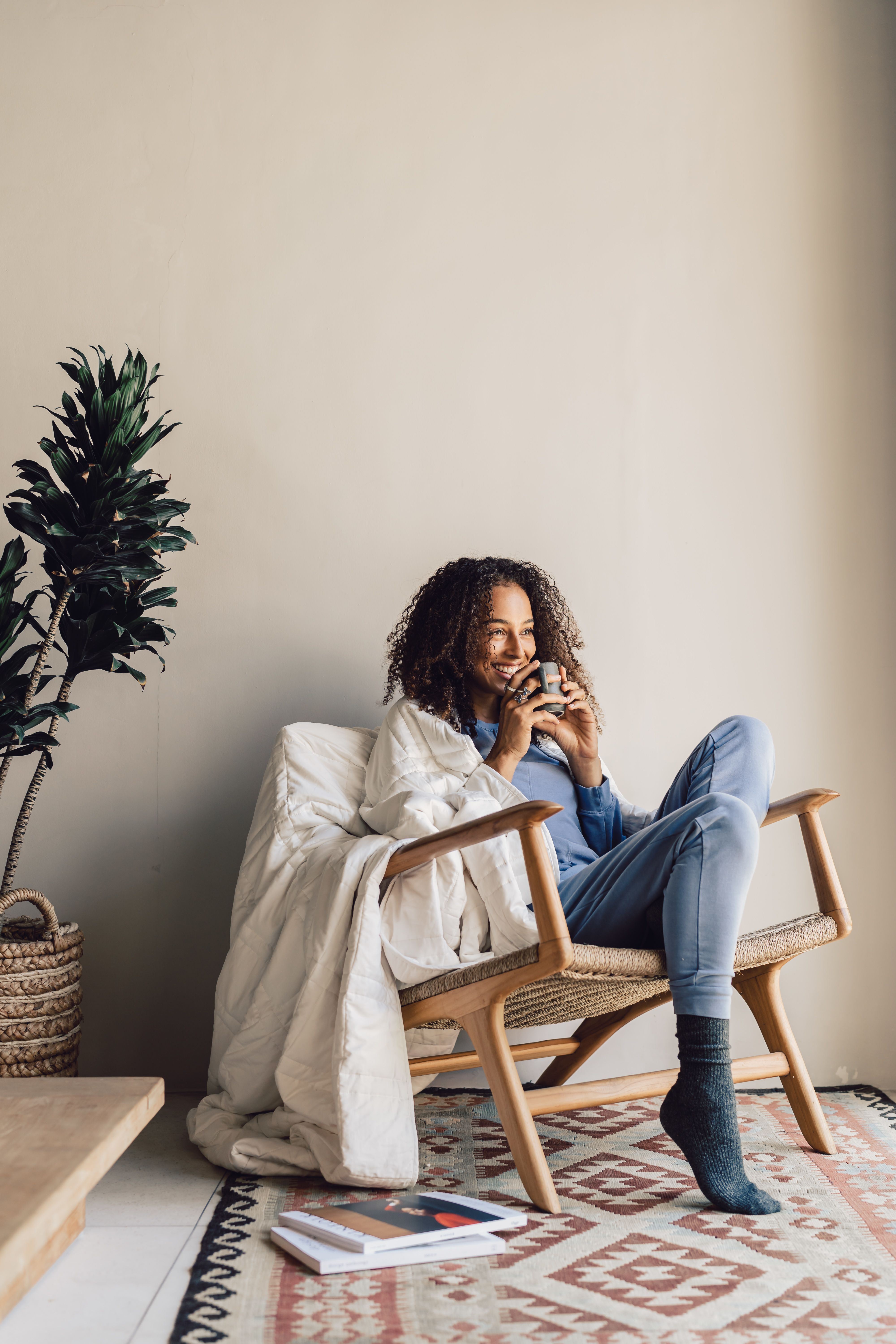 Model sitting in chair with Baloo Living weighted blanket