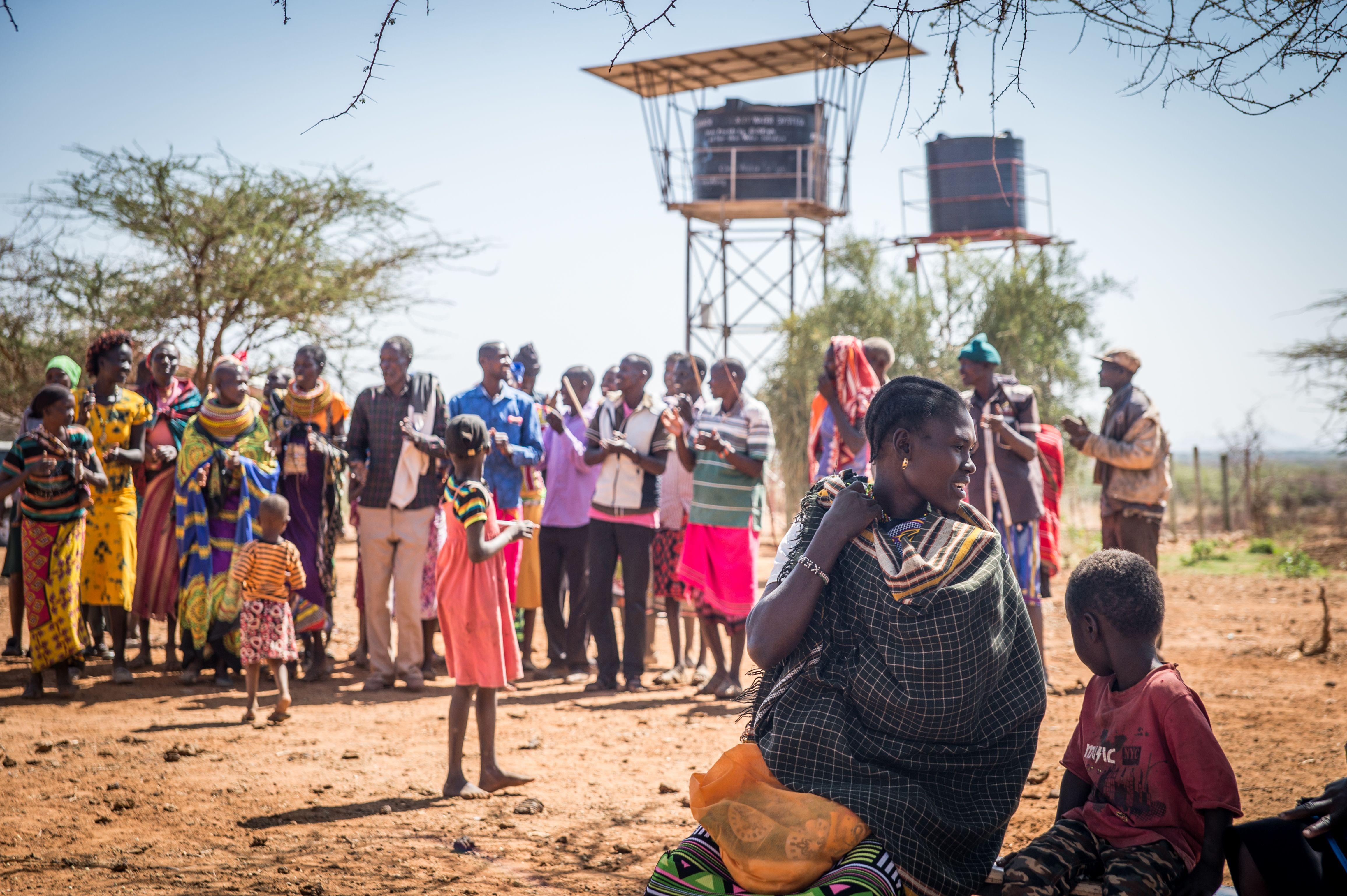 Community gathered around Well Aware water tanks - Alamach, Kenya