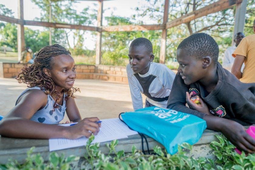 Karen conducts a community survey with two boys - Sauti Kuu