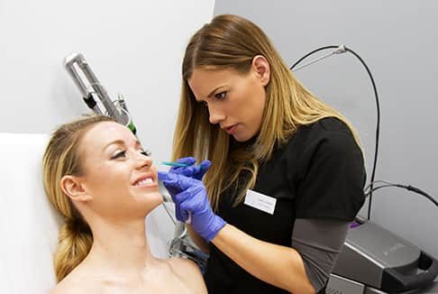 Female nurse performing a botox injection on the side of the face