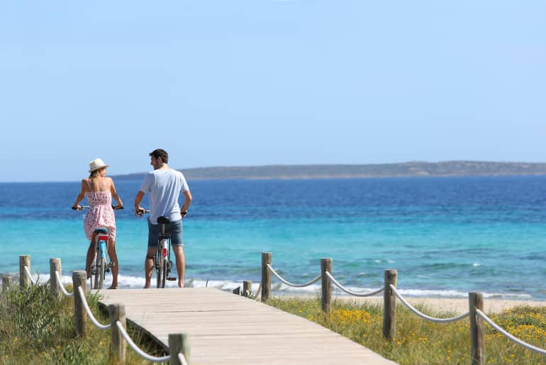 Paar mit Rad am Strand in Ibiza