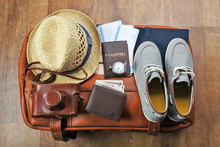 Tasche mit Reisepass, Kammera, Schuhe und Hut für den Urlaub