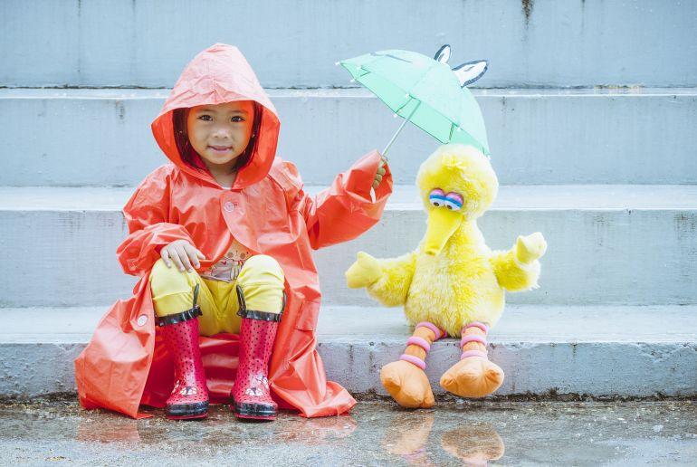 Kind mit Kuscheltier im Regen