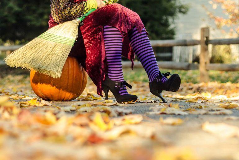 Hallowenn Hexe sitzt auf Kürbis