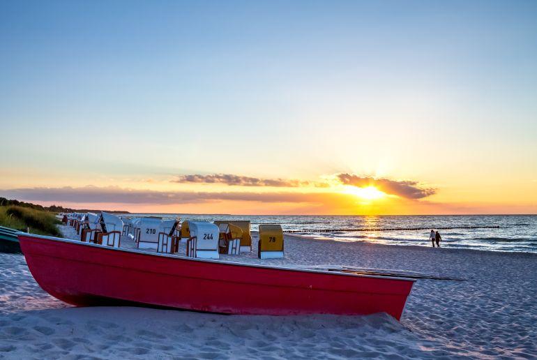 Strandkorb und Boot am Strand bei Sonnenuntergang