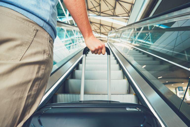 Mann am Flughafen mit Koffer auf der Rolltreppe