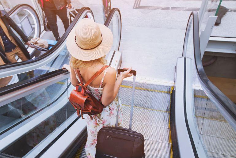 Frau mit Koffer auf Rolltreppe