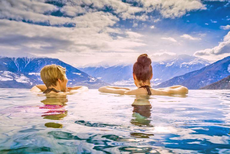 Frauen im Infinitypool mit Blick über Alpen