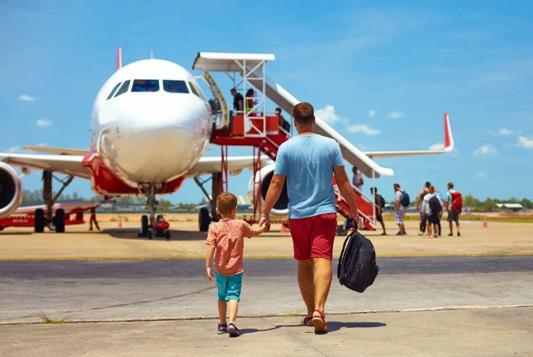 Mann mit Kind auf dem Weg zum Fliugzeug