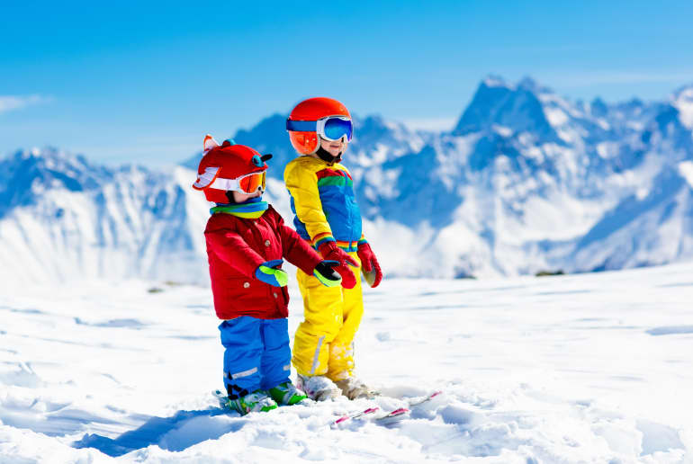 Kinder in Skianzügen auf dem Berg im Winter