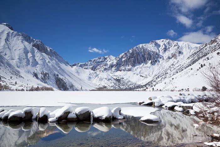 Destinos invierno españa: lago y montañas nevadas en sierra nevada granada