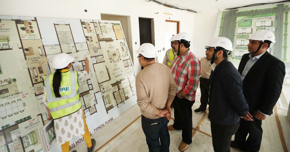Shri Vikas Sharma and members of the delegation learning about the floor plans of government accommodation