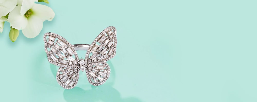 Spring Fling. Fabulous Styles To Welcome The New Season. Image Featuring A Butterfly Ring on a Light Blue Background