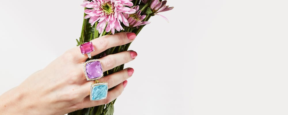 Cheerful Jewelry. Sweet Styles in Full Bloom. Image Featuring Model Holding Flowers and Wearing Gemstone Rings