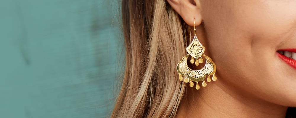 Gold earrings elevate your outfit with glowing pairs. Image Featuring Model Wearing Gold Drop Earrings