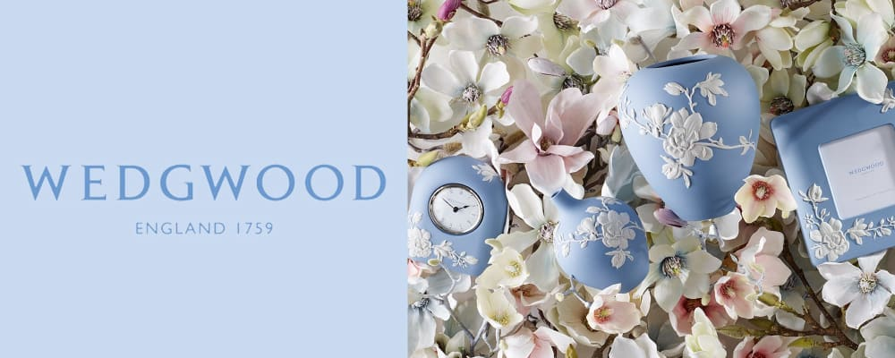 Wedgwood England 1759. Image of blue decorative clock, vases and picture frame on flowers.