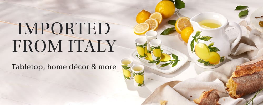 Imported From Italy -- Drinkware, Home Decor and More. The Extraordinary Italian Jewelry. In collaboration with the Italian Trade Agency, the Ministry of Econimic Development and Confindustrua-Federorafi. Image shows lemon design pitcher and glasses with bread.