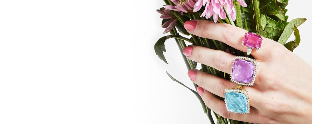 Fabulous rings collect every chic style. Image Featuring A Model's Hand Holding Flowers Wearing Gemstone Rings